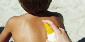 rear view of a young boy getting his back sprayed with sunscreen lotion